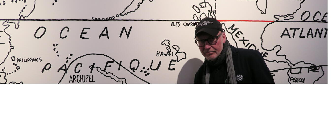 Bruce Barber pointing to New Zealand in his appropriation of 'The Surrealist Map of the World,' 1929. Personal Structures: Open Borders, Palazzo Mora, Venice. Image: Contemporary HUM.