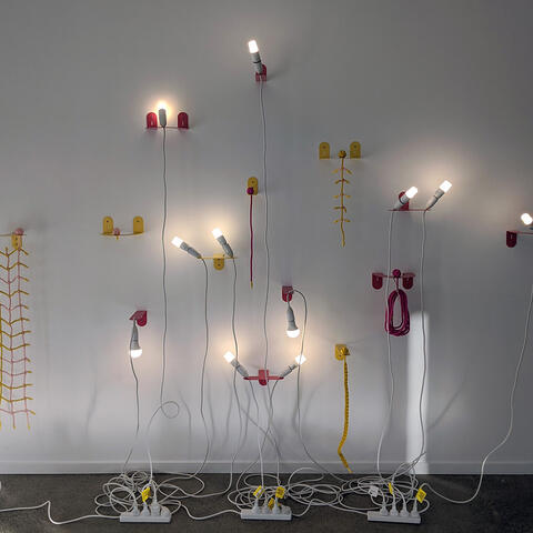 Various red and yellow light fittings with visible power cables fixed to a gallery wall.