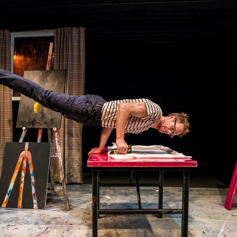 Thom Monckton performs a handstand plank on a table with a stapler