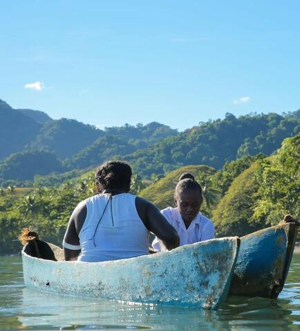 Image from Vai in Papua New Guinea - two women sit on a boat on the water with trees behind them