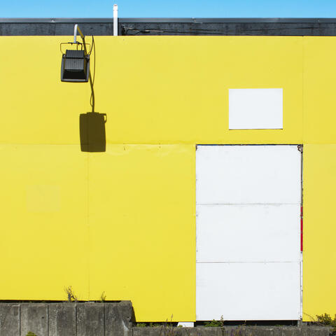 Image of a door on yellow background by Kira Sampurno