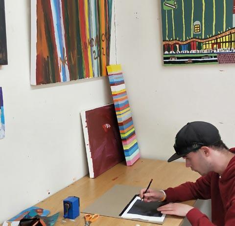 A White Room artist at work, surrounded by art on the walls