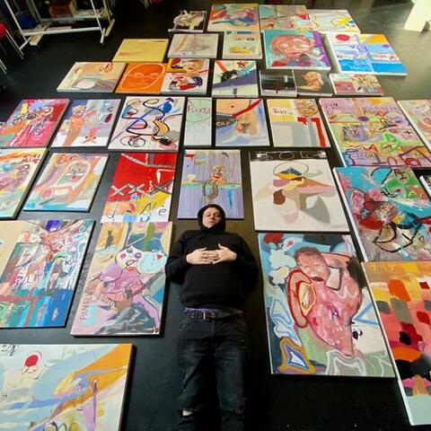 An artists lies on the floor, surrounded by artwork
