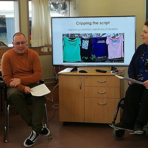 """Stace Robertson and Erin Gough present a disability training workshop to staff at Arts Access Aotearoa. A TV screen has a photo of tee-shirts on the washing line and a heading """"Cripping the script"""""""