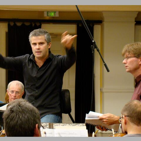 Tecwyn Evans conducting NZSO with composer Anthony Ritchie looking on