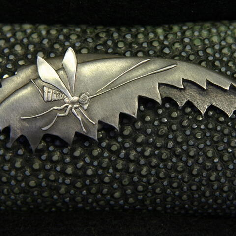 Katana menuki, showing ichneumonid wasp (that parasitises the kahukura pupa) above Ongaonga leaf. Hand-carved sterling silver.