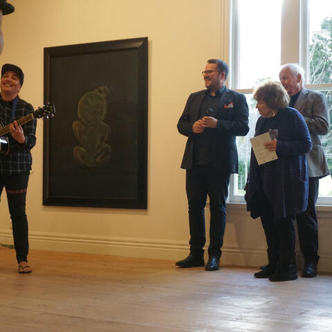 Ra Gossage performs at the opening of 'Still No Answer', in front of a work by Dr Fiona Pardington. Image: Annie Pokel