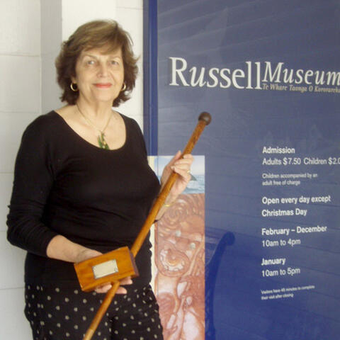 Lorraine Hill, chairperson of Russell Centennial Trust Board holding flagstaff pieces recently returned to Russell.