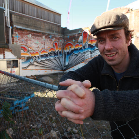Art of Recovery: Johnny Moore stands in front of Smash Palace street art.