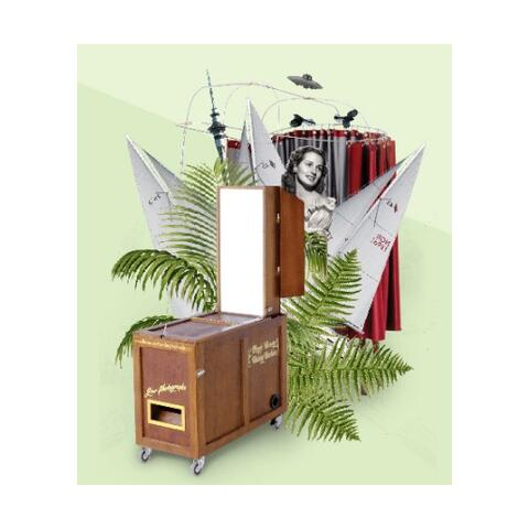an image of the amazing travelling photobooth with an assortment of items - ferns, glamourous models, spaceships and sailboats, bursting from it.