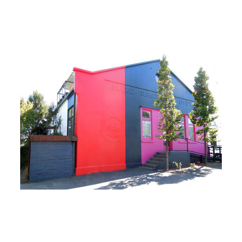 Image of the Refinery ArtSpace Front Building. Painted in bright red, dark grey and pink. Entrance in between 2 Kauri Trees, not visible in the image.