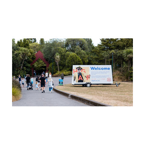 """An image showing a large billboard, reading """"Welcome"""" next to a footpath at the entrance to Hamilton Gardens"""