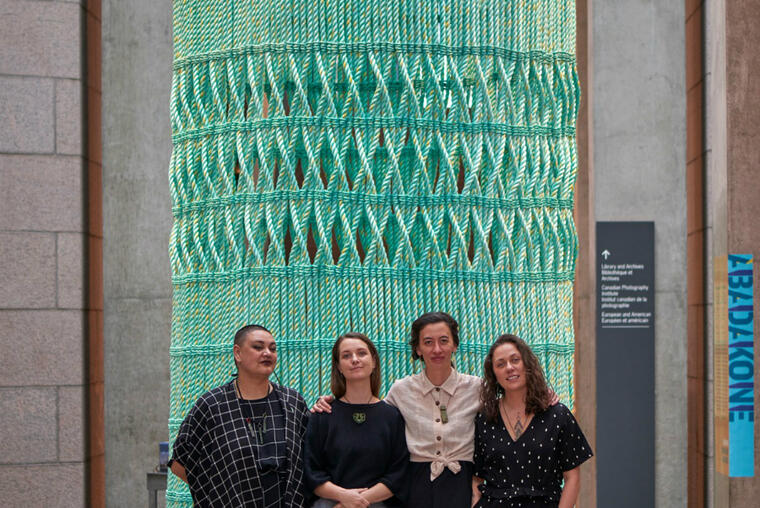 Mata Aho Collective with a portion of their monumental, handwoven sculpture, Aka
